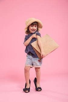 Grappig meisje is een fashionista in de schoenen van de moeder