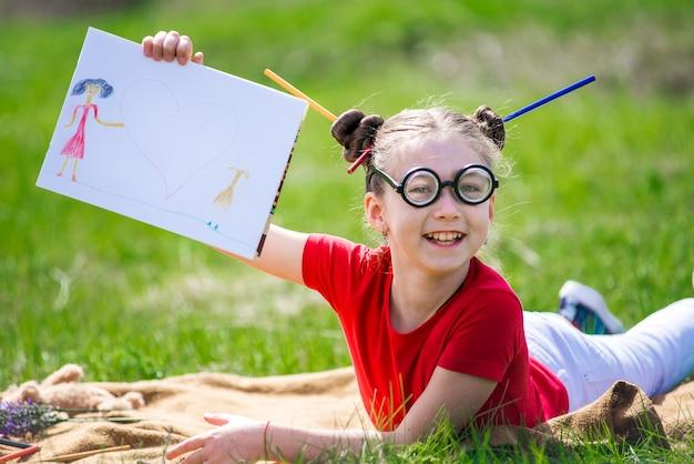 Grappig meisje met bril in het park trekt een potlood in album. tekening moeder en dochter