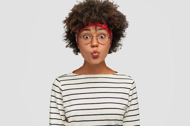 Grappig meisje met donkere huid vouwen lippen voor het maken van een kus, staart met uitgestoken ogen, maakt grimas, draagt zwart-wit gestreepte jas