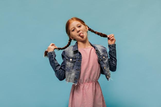Grappig meisje met gemberhaar en sproeten in gestreepte rode jurk en modieuze coole jas met tongen op blauwe muur