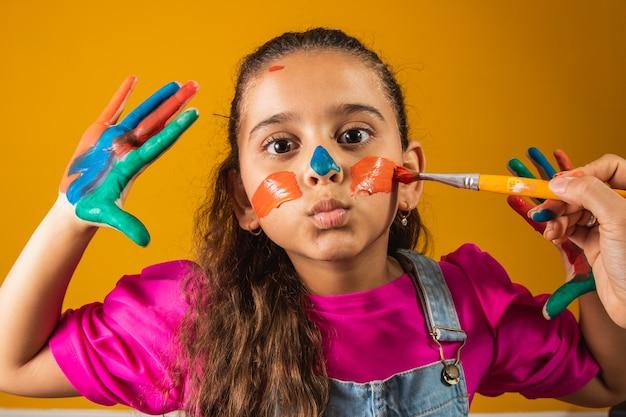 Grappig meisje met handen beschilderd met gekleurde verf. meisje wordt beschilderd met verf en penseel