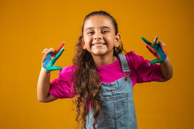Grappig meisje met handen geschilderd in gekleurde verf.