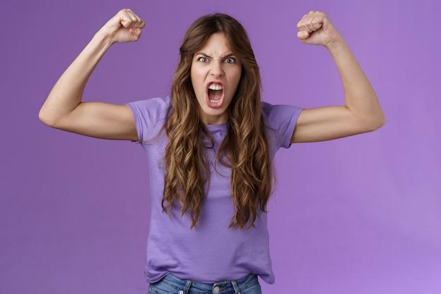 Grappig meisje met krullend haar dat handen opsteekt vuist pomp toon spieren schreeuwen gedurfd cool schreeuwen aangemoedigd gemotiveerd winnen grimassen sterke krachtige vrouw vieren overwinning voel als kampioen