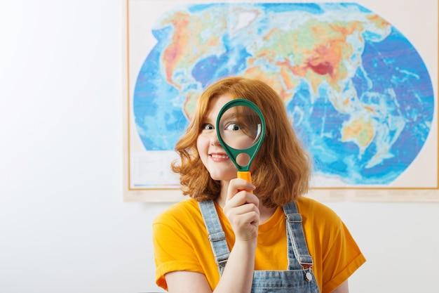 Grappig meisje met meer magnifier tribunes bij geografische kaart