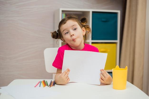 Grappig meisje met paardenstaarten in een roze t-shirt met een leeg wit papier aan de tafel in de kamer