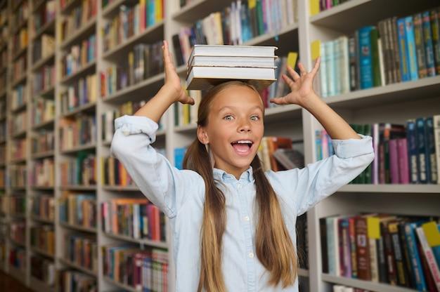 Grappig meisje met paardenstaarten poseren voor de camera in de bibliotheek
