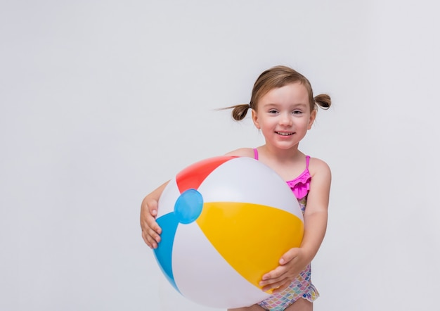 Grappig meisje met paardestaarten in een zwempak en een opblaasbare bal op een geïsoleerd wit