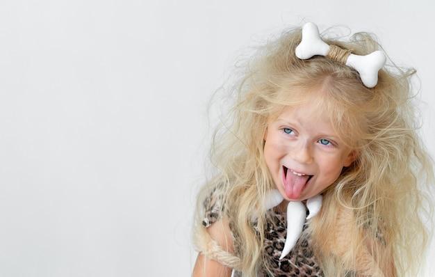 Grappig meisje met tong uit en ruig haar in het kostuum van de holbewoner