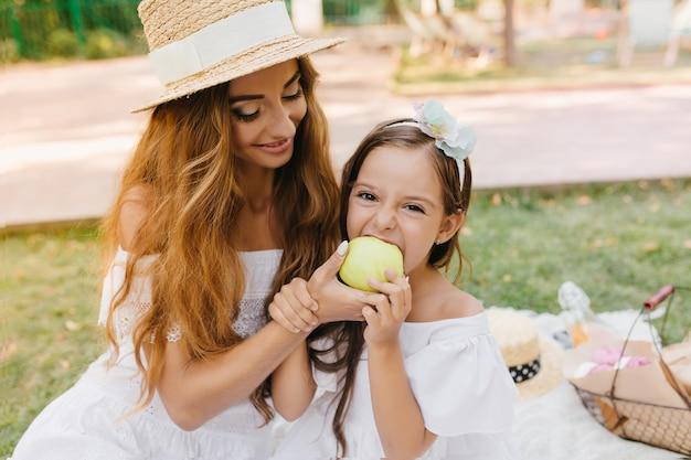 Grappig meisje neemt een hap van een grote groene appel die haar mooie moeder vasthoudt. outdoor portret van lachende jonge vrouw in elegante hoed dochter voeden met lekker fruit in zonnige dag.