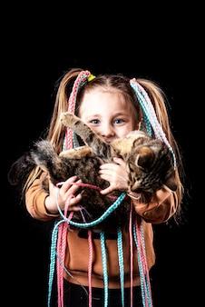 Grappig meisje op een zwarte achtergrond met afro-elastische banden, pigtails op elastiek, een kat met uitpuilende ogen koel houden
