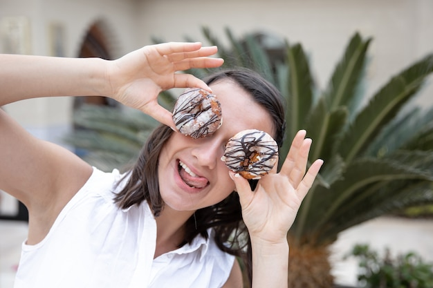 Grappig meisje poseren met donuts in de zomer buiten. vakantie en vakantieconcept.