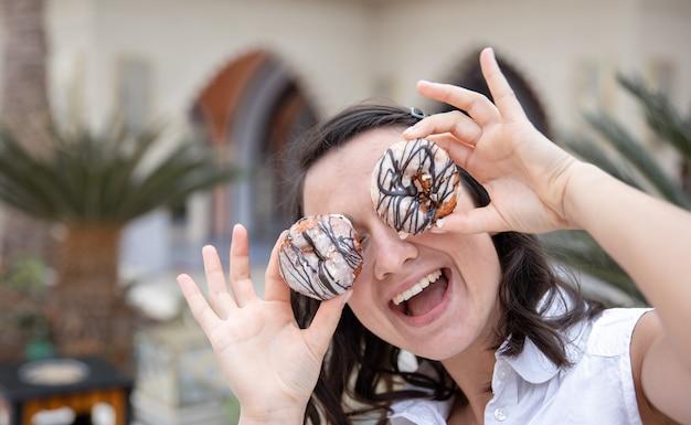 Grappig meisje poseren met donuts in de zomer buiten