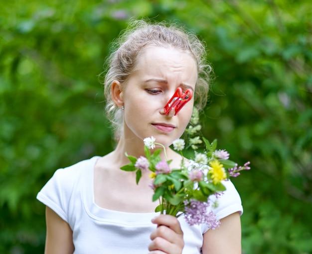 Grappig meisje probeert wanhopige maatregelen om lenteallergieën voor bloemen te bestrijden. vrouw die haar neus beschermt tegen allergenen met wasknijper