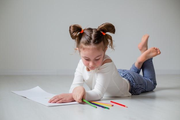 Grappig meisje tekenen in een album met kleurpotloden thuisonderwijs kleuterschool