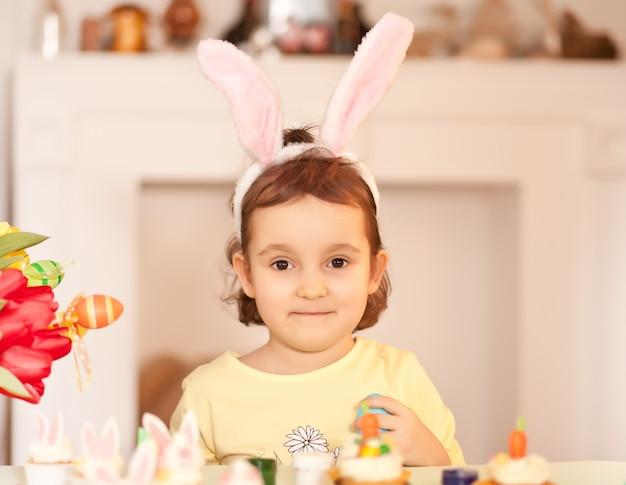 Grappig meisjeskind dat konijntjesoren en thuis met paasei in hand draagt.