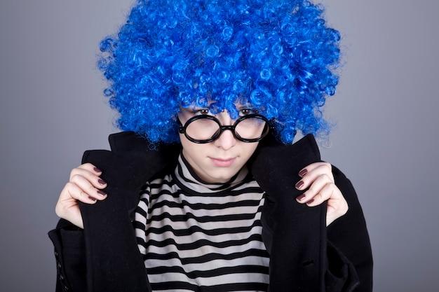 Grappig mode blauw haarmeisje in glazen en zwarte jas.