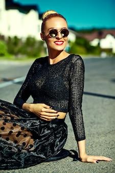 Grappig modieus sexy het glimlachen mooi jong blond vrouwenmodel die in kleren van de zomer de zwarte hipster in de straat zitten