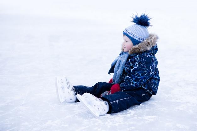 Grappig moment - schattige kleine jongen viel op de ijsbaan