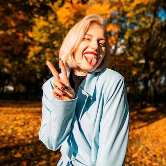 Grappig mooi gelukkig blond meisje in een modieuze jas toont de tong en het teken van vrede in de herfstnatuur met gele herfstbladeren bij zonsondergang