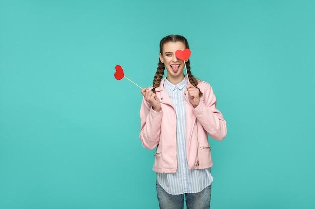 Grappig mooi meisje in casual stijl, vlecht kapsel en roze jas, permanent en rood hart stickers te houden en kijken naar camera met tong uit, indoor, geïsoleerd op blauwe of groene achtergrond