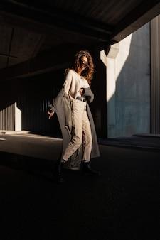 Grappig mooi meisjesmodel met krullend haar in modieuze kleding met een vintage lange jas die op straat in het zonlicht loopt. stedelijke vrouwelijke stijl en elegante mode