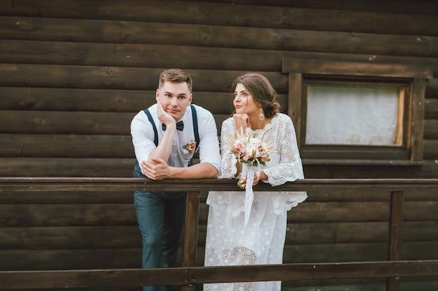 Grappig onlangs echtpaar, glimlachende bruid donkerbruine jonge vrouw met het boeket van de bohostijl met bruidegom