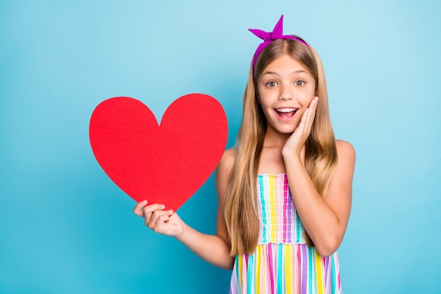 Grappig opgewonden romantisch meisje houdt een groot rood papieren hart vast