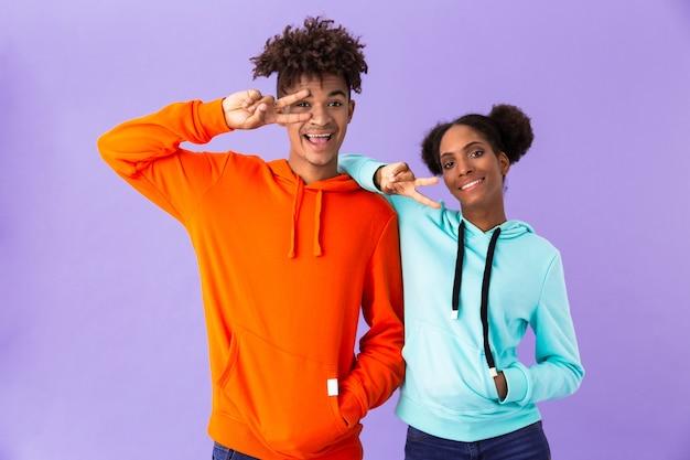 Grappig paar in kleurrijke kleding glimlachend en vredesteken tonen, geïsoleerd over violette muur