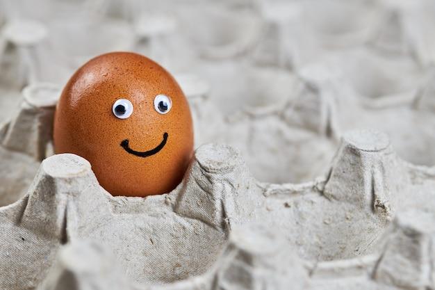 Grappig paasei-gezicht in papieren eierrekje. vers natuurlijk ei, kopieer ruimte. gelukkige ochtend, ontbijt emotie concept. kwaliteitslevering zonder schade.