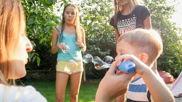 Grappig portret van een gelukkig, vrolijk jong gezin dat zeepbellen blaast en opvangt in de achtertuin van het huis