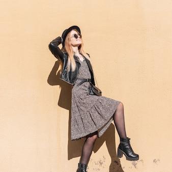Grappig portret van een mooie gelukkige vrouw met een zonnebril in modieuze look met jurk, leren jas en schoenen die zich voordeed in de buurt van een beige muur. mode stijl en schoonheid