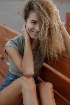 Grappig portret van een mooie jonge stijlvolle vrouw met krullend haar met een glimlach in modieuze vrijetijdskleding op straat