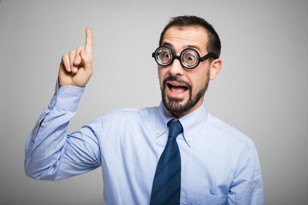 Grappig portret van een opgeheven nerdmens met zijn vinger, ideeconcept