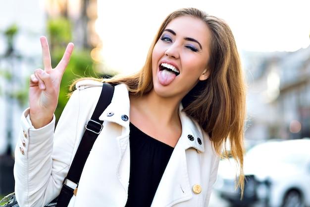 Grappig portret van gelukkig blond meisje, grappige gezichten maken en tong tonen op straat, herfsttijd, rust in de stad.