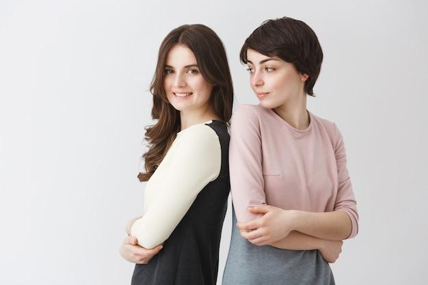 Grappig portret van gelukkige lesbische paar poseren samen in bijpassende outfits of universitair afstuderen album. meisje dat de pose van haar vriendin voor foto probeert te herhalen.