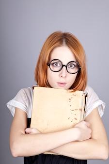 Grappig roodharig meisje met oud boek.