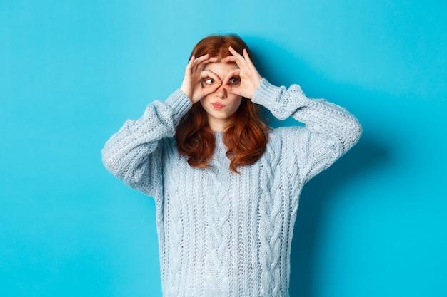 Grappig roodharig vrouwelijk model in trui, starend naar camera door vingersbril, interesse en verbazing tonend, staande over blauwe achtergrond
