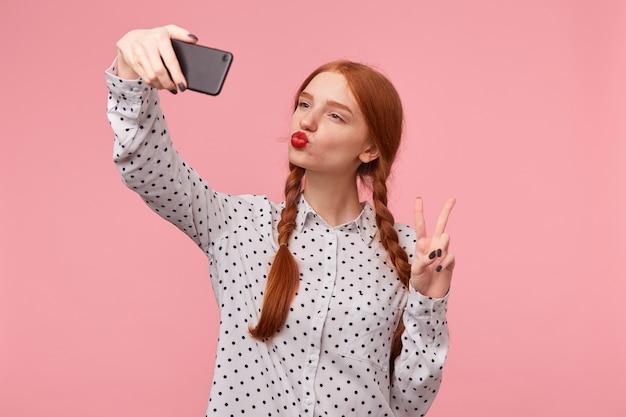 Grappig roodharige meisje stuurt luchtkus met rode lippen, kijkt naar telefoon, geïsoleerd, toont met haar vingers een vredesteken of overwinning, maakt selfie op haar telefoon