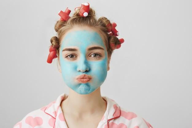 Grappig schattig meisje in haarkrulspelden en gezichtsmasker pruilen, adem inhouden