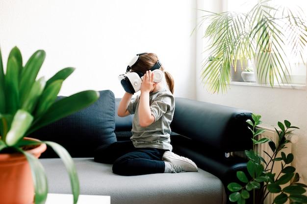 Grappig schattig meisje kijken naar iets dat wordt weergegeven in bril van virtual reality, zittend op de bank. modern technologieconcept