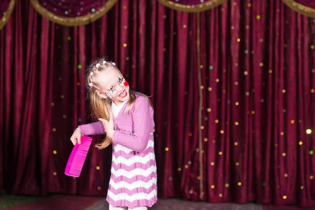 Grappig schattig meisje met geschilderd gezicht dat haar blonde lange haar kamt met een enorme roze kam tijdens een theatervoorstelling op het podium, met een kersenkleurig gordijn achter haar