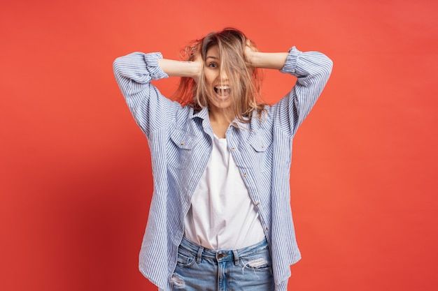 Grappig, schattig meisje met plezier tijdens het spelen met haar geïsoleerd op een rode muur