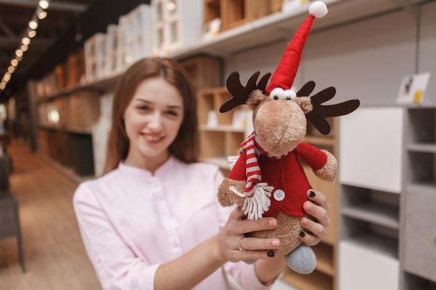 Grappig schattig rendierstuk speelgoed in de handen van gelukkige vrouw die voor kerstmisgoederen winkelt