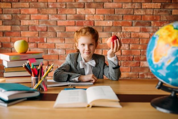 Grappig schoolmeisje met appel aan de tafel zitten
