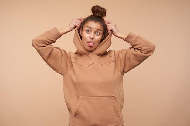 Grappig schot van jonge mooie bruinharige dame met knotkapsel die vrolijk tong aan de voorkant toont terwijl ze haar kap opneemt, geïsoleerd over beige muur