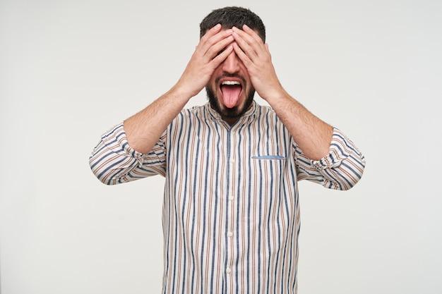 Grappig schot van jonge mooie brunette bebaarde man met kort kapsel die zijn ogen bedekt met opgeheven handen en zijn tong uitsteekt terwijl hij over een witte muur staat