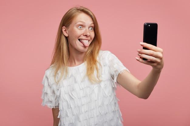 Grappig schot van jonge vrolijke roodharige dame die haar tong uitsteekt en groen-grijze ogen rondt terwijl ze een foto van zichzelf maakt met haar mobiele telefoon, geïsoleerd op roze achtergrond