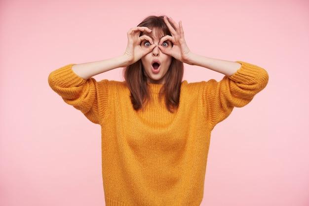 Grappig schot van mooie jonge donkerharige dame die met grote ogen en geopende mond kijkt, opgeheven handen op haar gezicht houdt terwijl zij over roze muur poseert