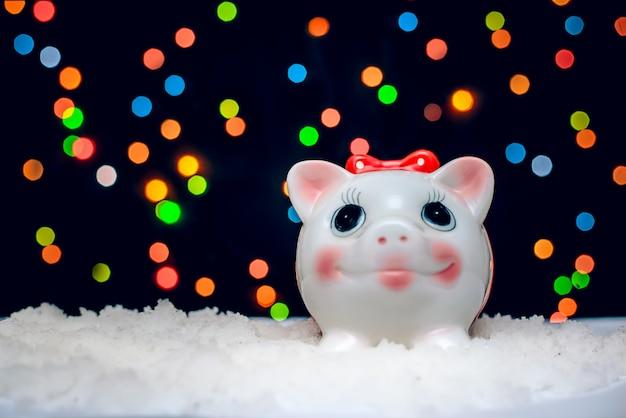 Grappig spaarvarken op een achtergrond van gekleurde lichten bij kerstmis