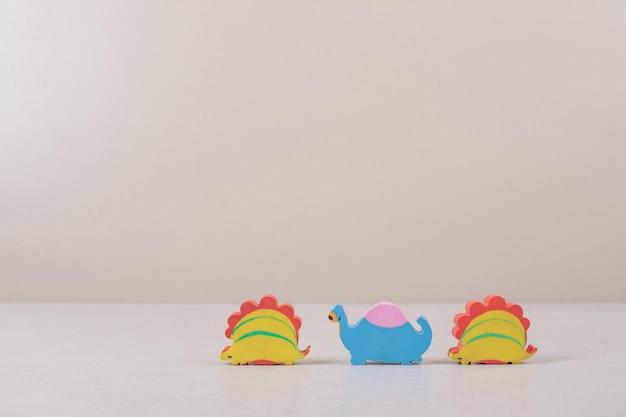 Grappig speelgoed van dinosaurussen op beige ruimte.